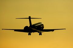 Silhouette of jet about to touch down. Stock Image