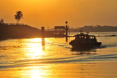 Silhouette of jetty and ferry in orange sun light Royalty Free Stock Photography