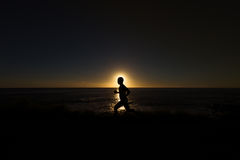 Silhouette of jogger along ocean horizon at sunset Royalty Free Stock Photo