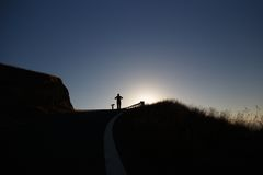 Silhouette of jogger on hillside at sunset Royalty Free Stock Photo