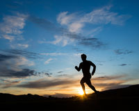 Silhouette of a jogger in sunset stock photography