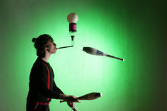 Silhouette of a juggler. With juggling pins on a green background royalty free stock images