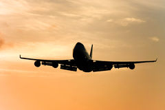 Silhouette of jumbo jet in flight. Silhouette of jumbo jet in flight at sunset Royalty Free Stock Image