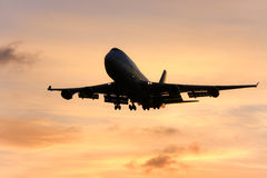 Silhouette of jumbo jet in flight. Silhouette of jumbo jet in flight at sunset Stock Photos