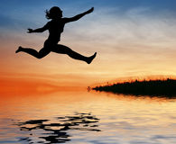 Silhouette jump girl on water Stock Photo
