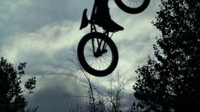 Silhouette of jumper, performing BMX mountain bike stock footage