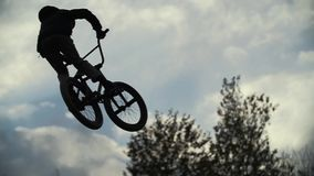 Silhouette of jumper, performing BMX mountain bike stock video footage