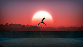 Silhouette of jumping ballet woman with skyline of skyscraper city in the background. Sunset with large sun. Stock Image