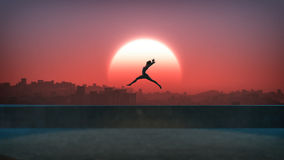 Silhouette of jumping ballet woman with skyline of skyscraper city in the background. Sunset with large sun. Royalty Free Stock Images
