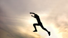 Silhouette of jumping boy against sky Stock Images