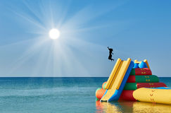 Silhouette of jumping girl with a trampoline in the water Royalty Free Stock Photos