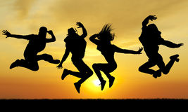 Silhouette jumping happiness people on sunset Stock Image