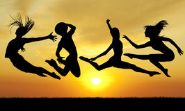 Silhouette jumping happiness people on sunset Royalty Free Stock Images