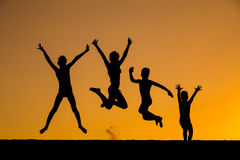 Silhouette of jumping kids against sunset Royalty Free Stock Images