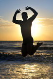 Silhouette of a jumping man. On the beach Stock Photo