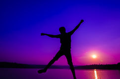 Silhouette jumping man Stock Images