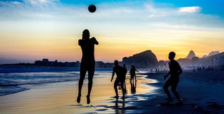 Silhouette of jumping man playing beach football on the background of beautiful sunset at Copacabana beach, Rio de Janeiro Stock Images