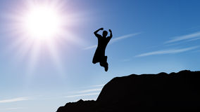 Silhouette of the jumping man from a rock. A shining sun with beams Royalty Free Stock Image
