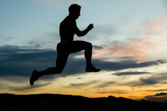 Silhouette of a jumping man in sunrise Stock Images