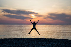 Silhouette of jumping man on sunrise background.  Stock Image