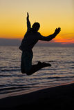 Silhouette of jumping man on sunrise background.  Royalty Free Stock Image