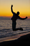 Silhouette of jumping man on sunrise background Royalty Free Stock Image