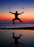 Silhouette jumping man and tossing stone Royalty Free Stock Images