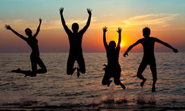 Silhouette of jumping people. On sunset background Stock Photography