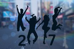 Silhouette of jumping people forming 2017 new year sign. Against city street in background Royalty Free Stock Photography