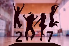 Silhouette of jumping people forming 2017 new year sign. Against dance studio in background Royalty Free Stock Photography
