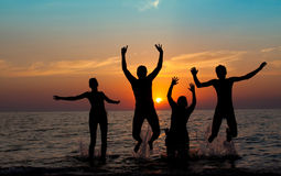 Silhouette of jumping people. On sunset background Royalty Free Stock Photography