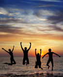 Silhouette of jumping people. On sunset background Royalty Free Stock Photo