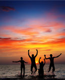 Silhouette of jumping people. On sunset background Stock Photos