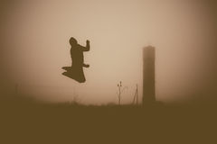 Silhouette of the jumping person in the evening. Royalty Free Stock Photography