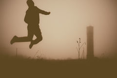 Silhouette of the jumping person in the evening. Stock Images