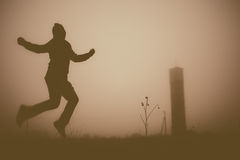 Silhouette of the jumping person in the evening. Royalty Free Stock Photo