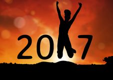 Silhouette of jumping person forming 2017 new year sign. During sunset Royalty Free Stock Images
