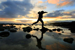 Silhouette jumping at sunset Stock Images