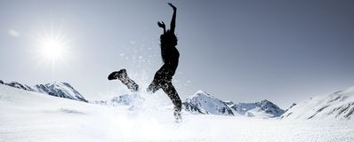 Silhouette of a jumping woman in Snowy Mountains royalty free stock image