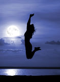 Silhouette jumping women on moon night. Silhouette of jumping women on moon night Royalty Free Stock Image