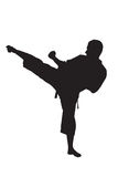 A silhouette of a karate man. Exercising against white background Royalty Free Stock Photo