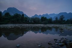 Scenic landscape in Vang Vieng, Laos at dusk. Silhouette of a karst limestone mountains and their reflections on the Nam Song River in Vang Vieng, Vientiane stock photos