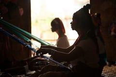 Silhouette of Kayan Lahwi girl is weaving. Stock Image