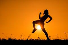 Silhouette of kick boxing girl exercising kick. Royalty Free Stock Photos