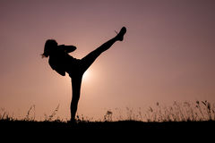 Silhouette of kick boxing girl exercising kick. Royalty Free Stock Photography