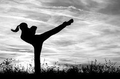 Silhouette of the kickboxing girl exercising outdoor in spring Royalty Free Stock Photography