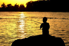 Silhouette of kid fishing Stock Photo