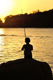 Silhouette of kid fishing near the beach Royalty Free Stock Photo