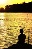 Silhouette of kid fishing near the beach Stock Photos