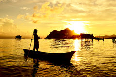 Silhouette of a kid paddling on a boat Stock Photography